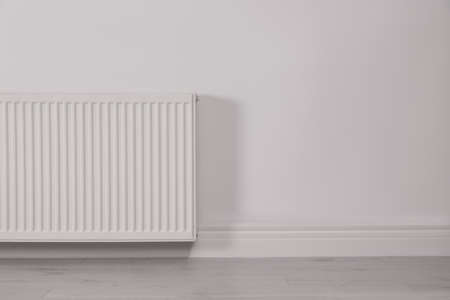 Modern radiator on white wall, space for text. Central heating system