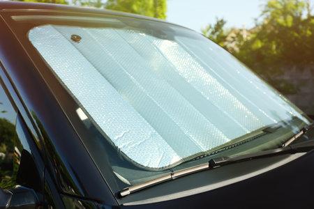 Sun shade under windshield inside car, closeup. Heat protection Stock Photo