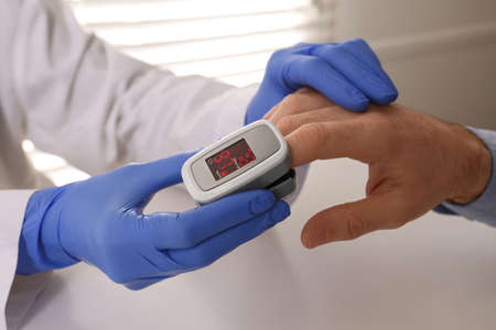 Doctor checking patient's oxygen level with pulse oximeter at light gray table, closeup