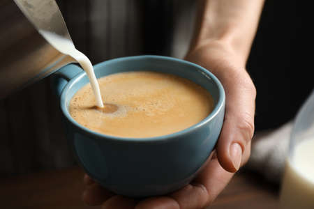 Woman pouring milk into cup of hot coffee, closeup