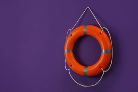 Orange lifebuoy and space for text on violet background. Rescue equipment Standard-Bild
