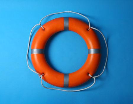 Orange lifebuoy on blue background. Rescue equipment