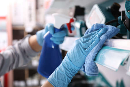 Woman cleaning shelf with rag and detergent in store, closeup 写真素材