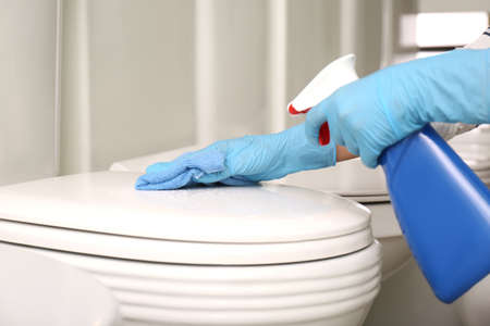 Woman cleaning toilet bowl with rag and detergent in
