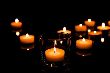Beautiful burning wax candles on black background Banco de Imagens
