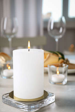 White burning wax candle on light table
