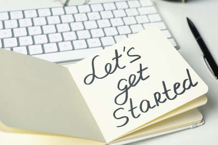 Notebook with phrase Let's Get Started and keyboard on white table