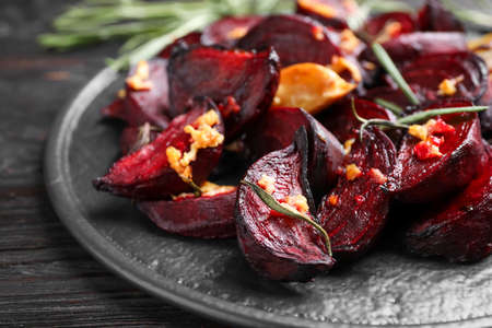 Roasted beetroot slices, garlic and rosemary on black wooden table, closeup