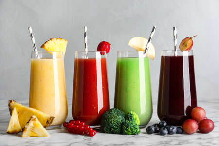 Glasses of delicious juices and fresh ingredients on white marble table 免版税图像
