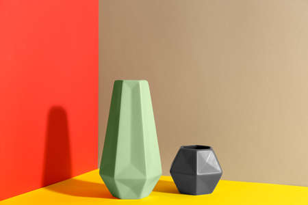 Stylish empty ceramic vases on color background