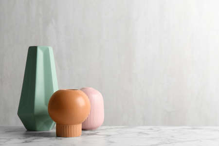 Stylish empty ceramic vases on white marble table, space for text