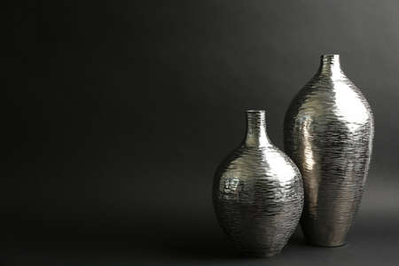 Stylish silver ceramic vases on black background, space for text