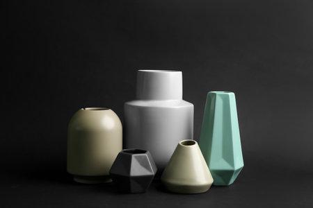 Stylish empty ceramic vases on black background