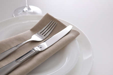 Elegant cutlery with napkin on white table, closeup