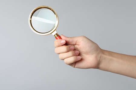 Woman holding magnifying glass on gray background, closeup. Find keywords concept