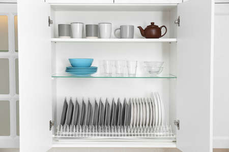 Open cabinet with different clean dishware in kitchen