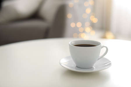 Cup of coffee on table indoors, space for text. Bokeh effect