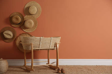 Wicker crib and straw hats on brown wall, space for text. Interior design