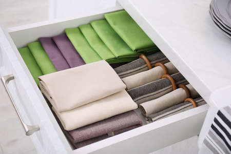 Open drawer with different folded towels and napkins in kitchen, closeup