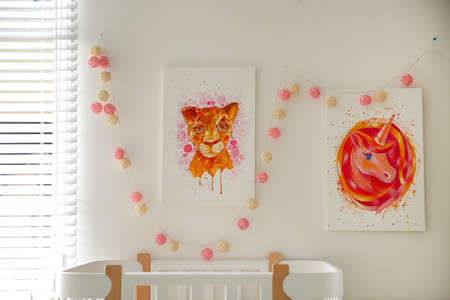 Cute pictures on white wall in baby room interior