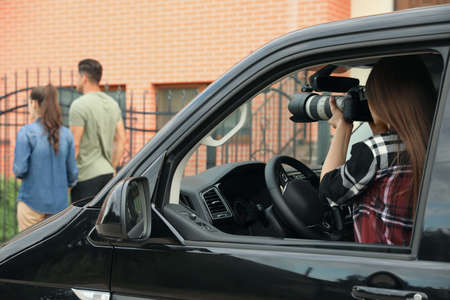 Private detective with camera spying from car Imagens