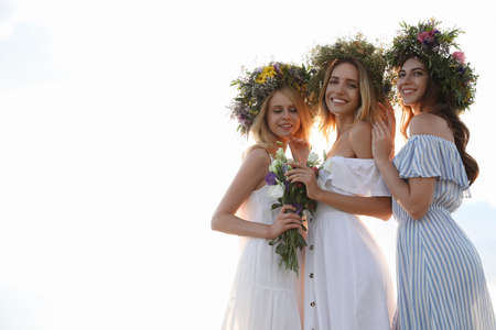Young women wearing wreaths made of beautiful flowers outdoors on sunny day