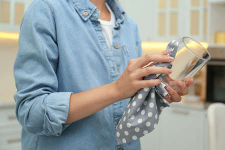 Woman wiping glass with towel in kitchen, closeup
