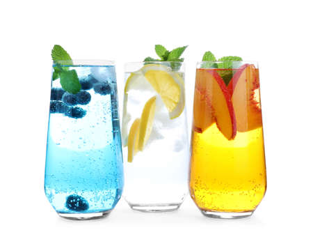 Different delicious lemonades made with soda water on white background