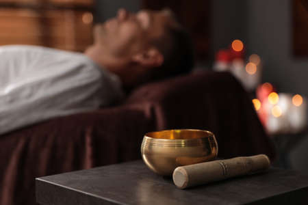 Man at healing session in dark room, focus on singing bowl Stock Photo