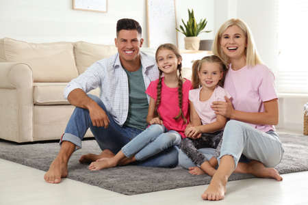 Portrait of happy family on floor at home