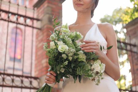 Gorgeous bride in beautiful wedding dress with bouquet near church, closeup
