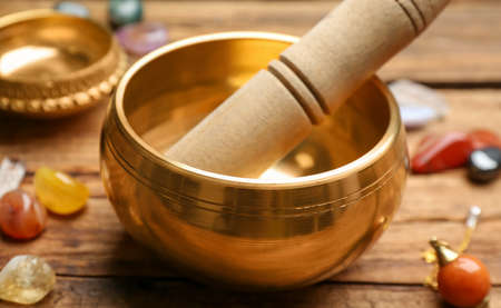 Golden singing bowl with mallet on wooden table, closeup. Sound healing