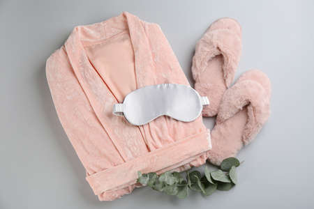Flat lay composition with house slippers, sleeping mask and robe on light background