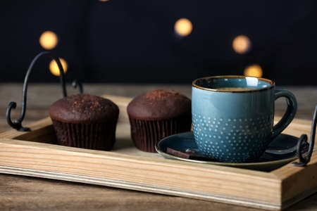 Cup of drink and chocolate muffins on wooden table against blurred lights, closeup