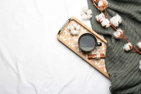 Flat lay composition with hot drink and warm plaid on white bedsheet, space for text