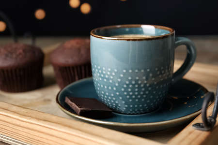 Cup with drink and piece of chocolate on wooden tray against blurred lights, closeup