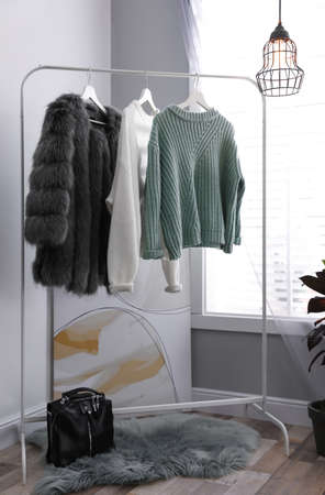 Stylish warm clothes on rack in dressing room interior