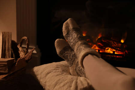 Woman in warm socks resting near fireplace with burning woods indoors, closeup