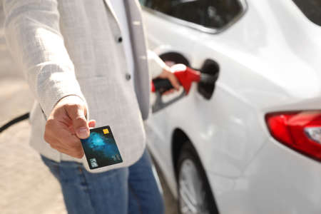 Man fills the car and giving credit card at gas station, closeup