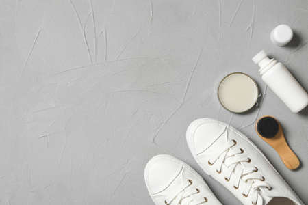 Flat lay composition with stylish footwear and shoe care accessories on light gray background, space for text