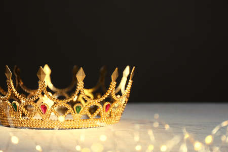 Beautiful golden crown and fairy lights on black background, space for text. Fantasy item