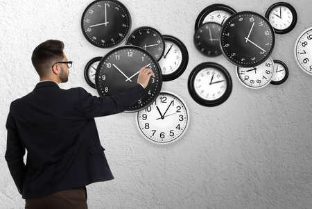 Time management concept. Businessman and different clocks on light grey background