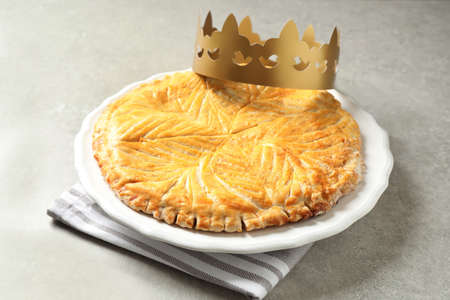 Traditional galette des Rois with paper crown on light gray table