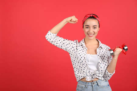 Woman with dumbbell as symbol of girl power on red background, space for text. 8 March concept