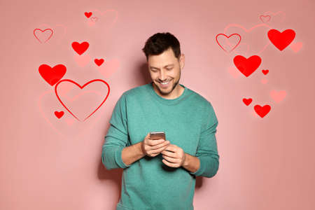 Man visiting dating site via smartphone on color background
