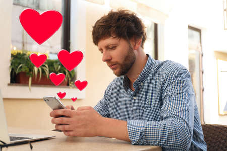 Man visiting dating site via smartphone in cafe