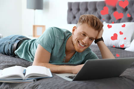 Young man visiting dating site via laptop indoors