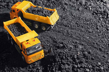 Toy tipper trucks with coal in field. Space for text