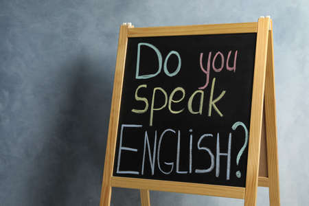 Blackboard with question Do You Speak English on grey background