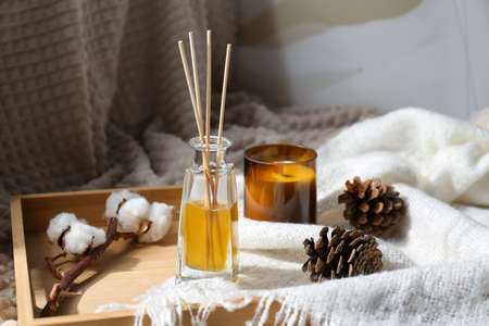 Reed air freshener, candle and pine cones on wooden tray indoors